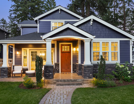 Beautiful new home shown with lights on at dusk.