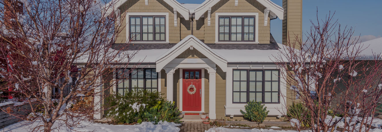 A beautiful home with snow on the roof and a bright red door.