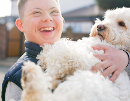 A young boy joyfully holds the family dog.