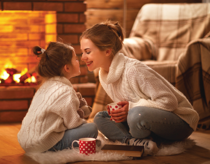 Mother and daughter sit in front of a fire while drinking hot cocoa.