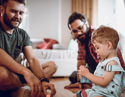 A toddler boy sitting on the floor plays with blocks while two men join him in play.