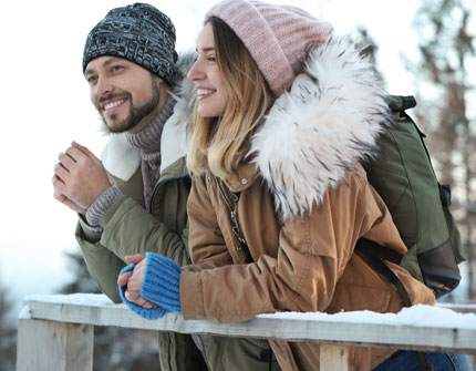 Couple with backpacks enjoying mountain view during winter vacation.