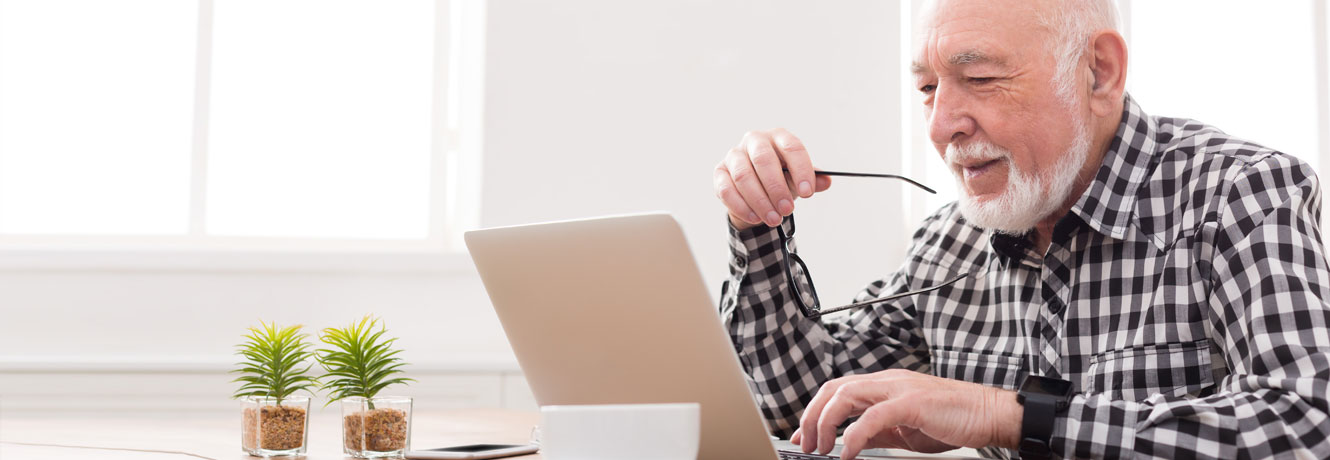 An older man checks his credit score on his laptop at home.
